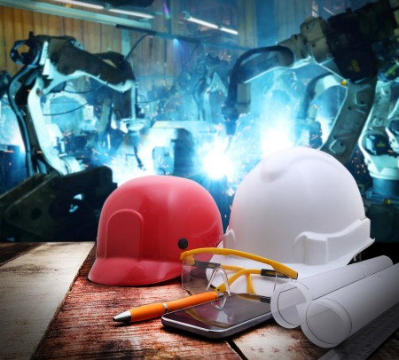 file of safety helmet and drawing on wood table with group robot welding automotive industrial background